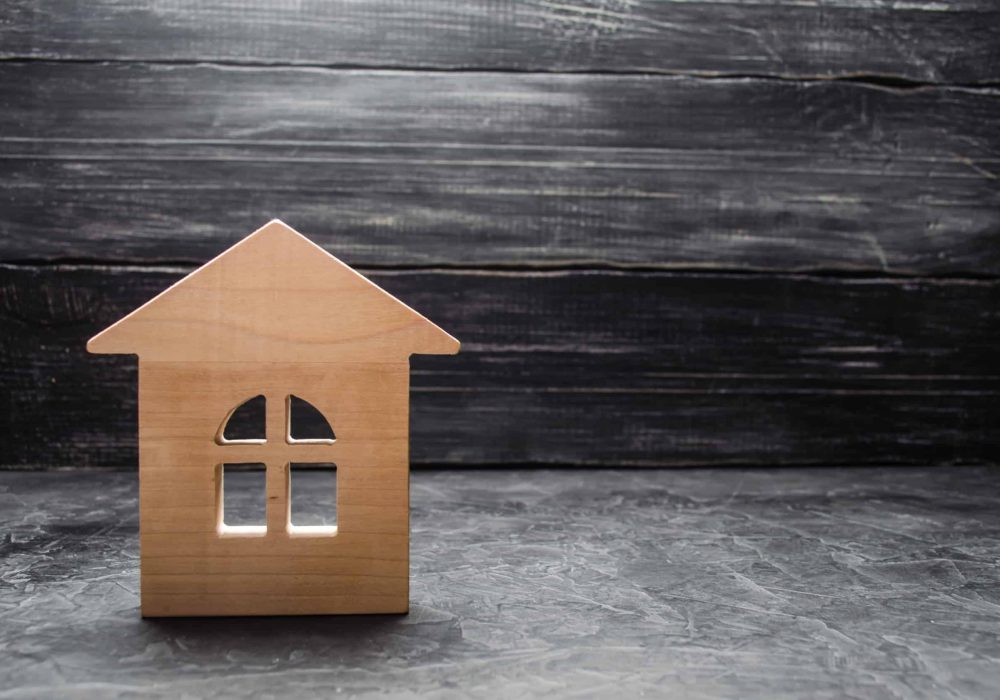 Wooden house on a dark background. The concept of buying the sale of real estate, rental housing. Realtor services. Property tax. Loan or loan for the purchase of real estate.